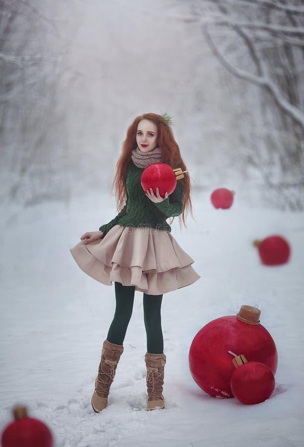 Het mooie roodharige meisje zoals een pop met reusachtige Kerstmis rode ballen loopt in de boskerstkaart van de de winterfee stock foto