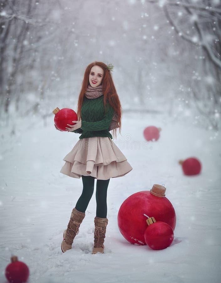 Het mooie roodharige meisje zoals een pop met reusachtige Kerstmis rode ballen loopt in de boskerstkaart van de de winterfee stock afbeeldingen