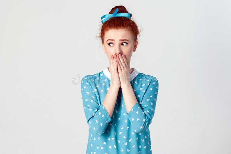 Het mooie roodharigemeisje in blauwe kleding doesn ` t wil geruchten of wat vertrouwelijke informatie uitspreiden royalty-vrije stock fotografie