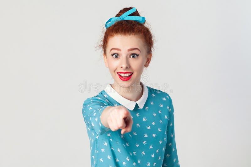 Het mooie roodharigemeisje, die blauwe kleding dragen, openend geschokt monden die wijd, bekijkt, richtend vinger camera hebben v royalty-vrije stock afbeelding
