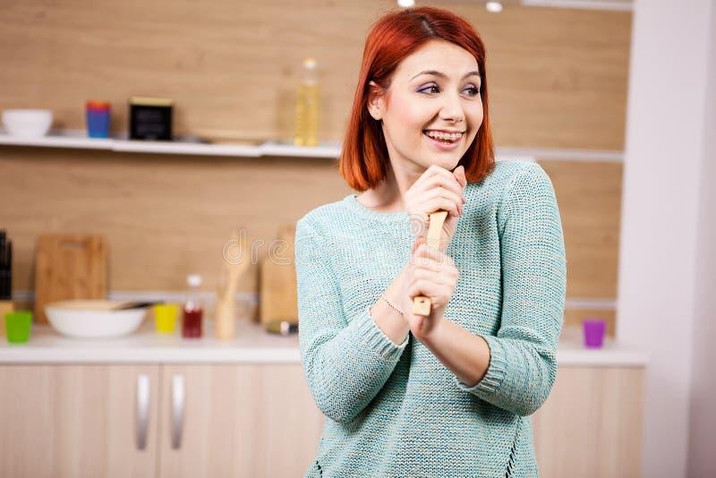 Het mooie roodharigevrouw zingen in de keuken royalty-vrije stock foto's