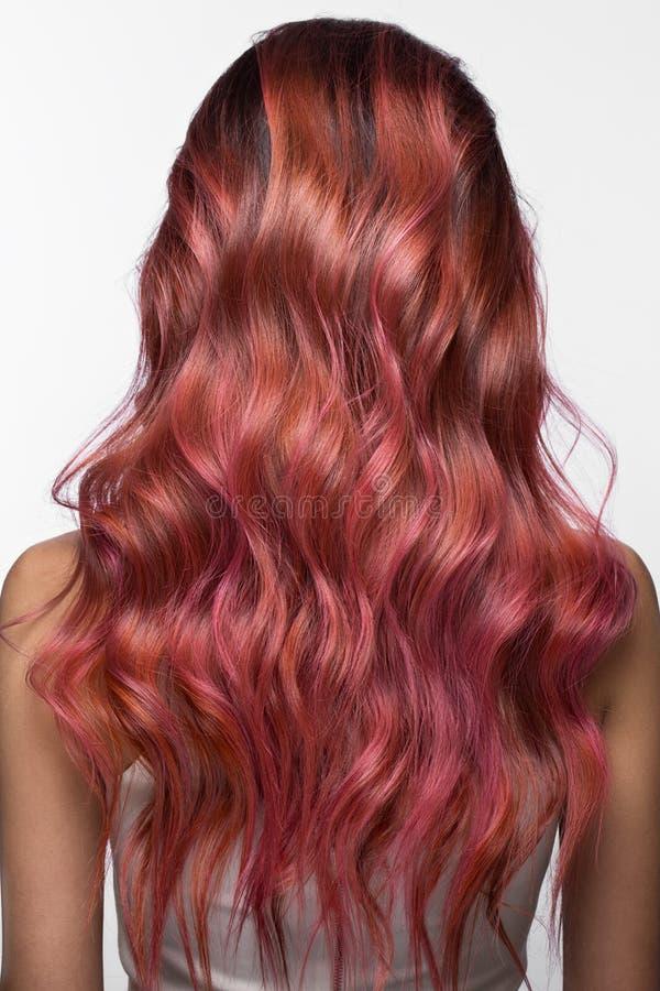 Het mooie roze-haired meisje in beweging met krult volkomen haar, Schoonheidssalon stock afbeeldingen