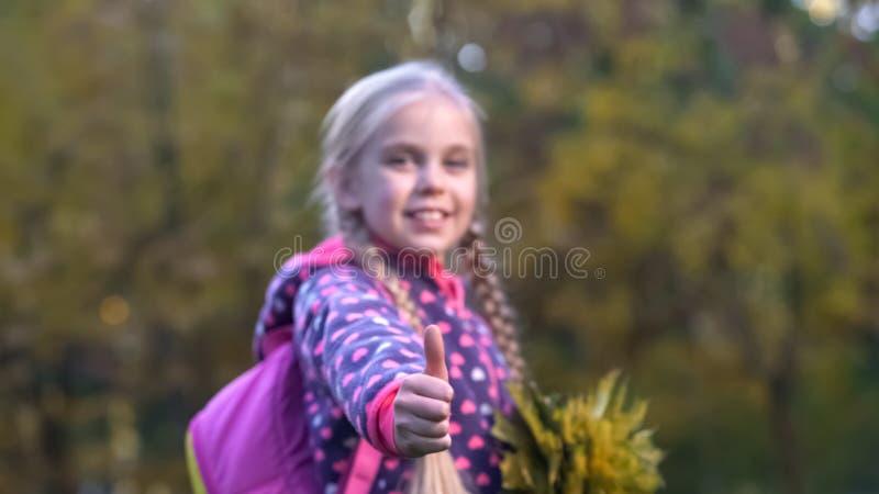 Het mooie schoolmeisje met camera bekijken en de herfstbladeren die beduimelt omhoog tonen royalty-vrije stock afbeeldingen