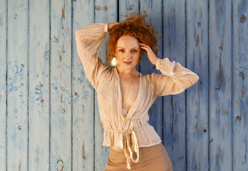 Het mooie sensuele meisje met lang golvend rood haar bundelde omhoog op haar hoofd stock fotografie