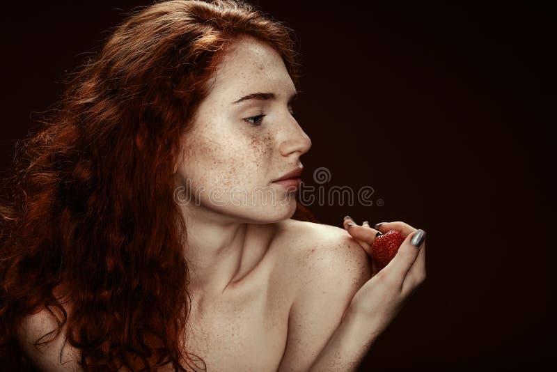 Het mooie sensuele naakte roodharigevrouw stellen met aardbei royalty-vrije stock afbeelding
