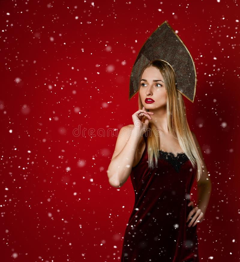 Het mooie sexy blonde Russische meisje in traditionele kokoshnikhoed, fluweel feestelijke kleding op een rode achtergrond, kijkt  royalty-vrije stock foto