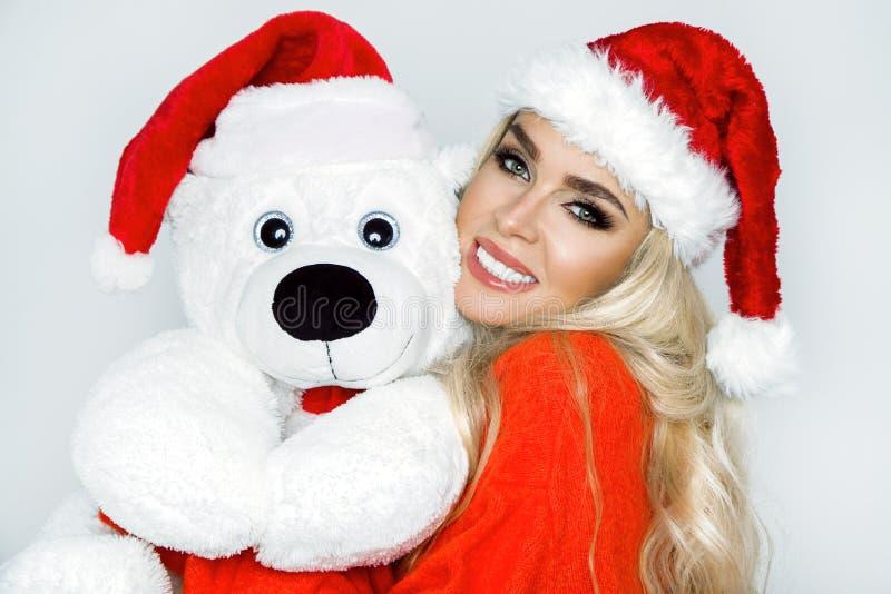 Het mooie sexy blonde vrouwelijke model gekleed in een Santa Claus-hoed omhelst een witte teddybeer in een rood GLB Christm stock afbeelding