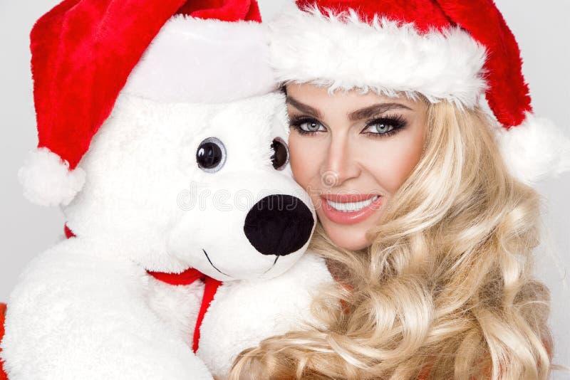 Het mooie sexy blonde vrouwelijke model gekleed in een Santa Claus-hoed omhelst een witte teddybeer in een rood GLB Christm royalty-vrije stock afbeeldingen