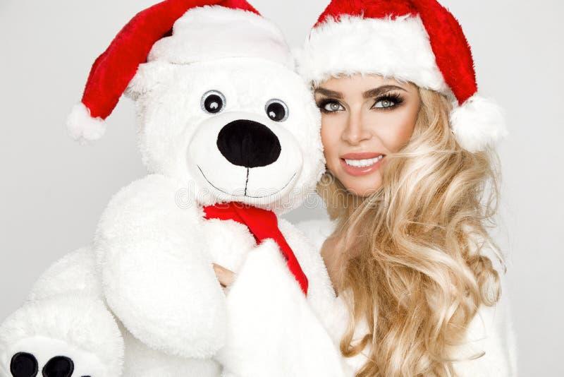Het mooie sexy blonde vrouwelijke model gekleed in een Santa Claus-hoed omhelst een witte teddybeer in een rood GLB Christm royalty-vrije stock foto