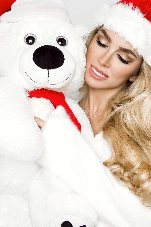 Het mooie sexy blonde vrouwelijke model gekleed in een Santa Claus-hoed omhelst een witte teddybeer in een rood GLB Christm royalty-vrije stock fotografie