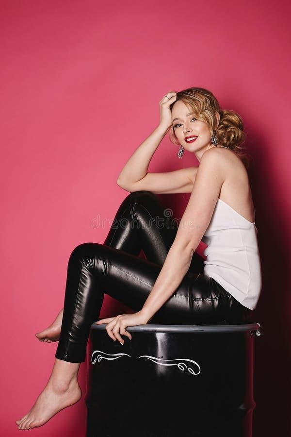 Het mooie, sexy en modieuze blondemeisje met rode lippen in witte t-shirt en zwarte beenkappen zit op een zwart vat bij rode back stock foto