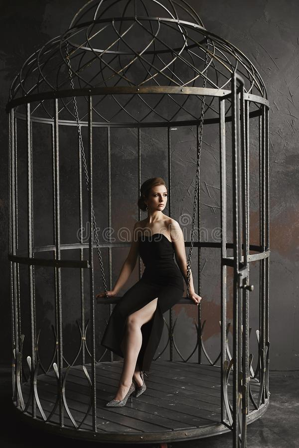 Het mooie, sexy en modieuze donkerbruine modelmeisje in lange zwarte kleding en heldere zilveren schoenen zit op een het hangende royalty-vrije stock fotografie