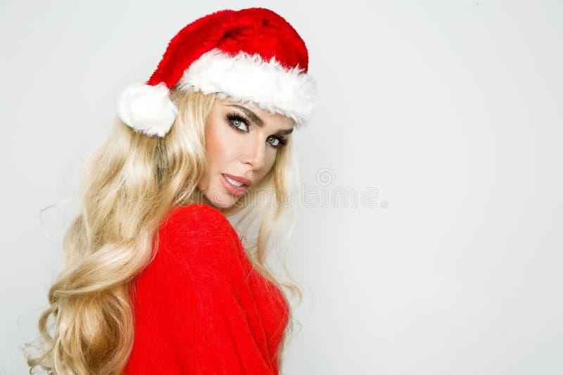 Het mooie sexy, glimlachende blondewijfje kleedde zich in een Santa Claus-hoed Schoonheids sensueel meisje voor Kerstmis royalty-vrije stock foto