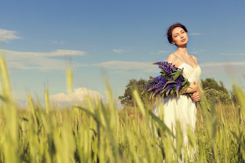 Het mooie sexy meisje met donker haar in witte sundress met een boeket van bloemenlupine loopt op het gebied met rogge op een zon royalty-vrije stock afbeelding