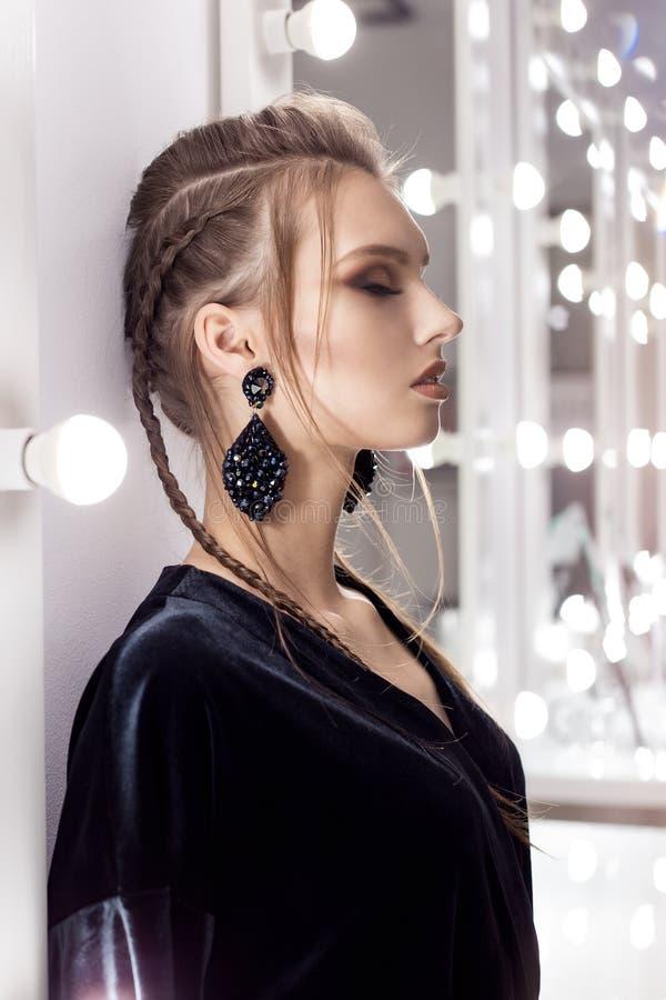 Het mooie sexy meisje met haar in de stijl van rots bevindt zich dichtbij de spiegel in de kleedkamer in een zwarte fluweeltoga m royalty-vrije stock foto's