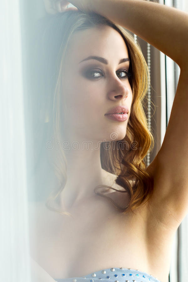 Het mooie sexy meisje met rood haar met grote volledige lippen met make-up zit dichtbij venster stock fotografie
