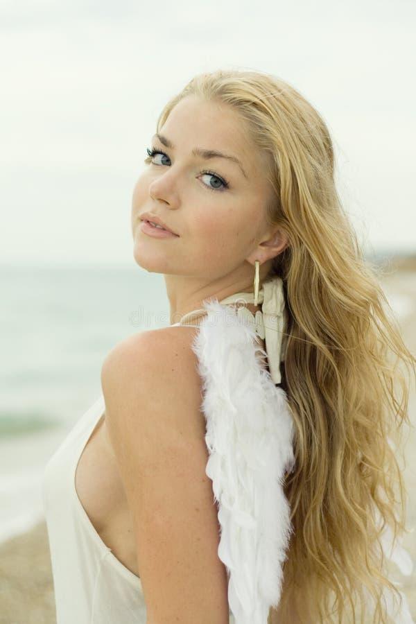 Het mooie sexy meisje met vleugels op zeekust royalty-vrije stock foto