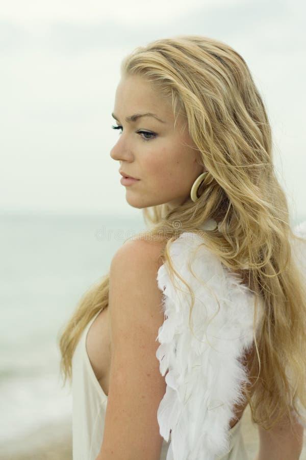 Het mooie sexy meisje met vleugels op zeekust stock afbeelding