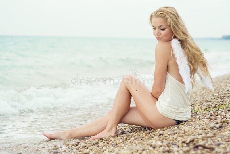 Het mooie sexy meisje met vleugels op zeekust stock foto's
