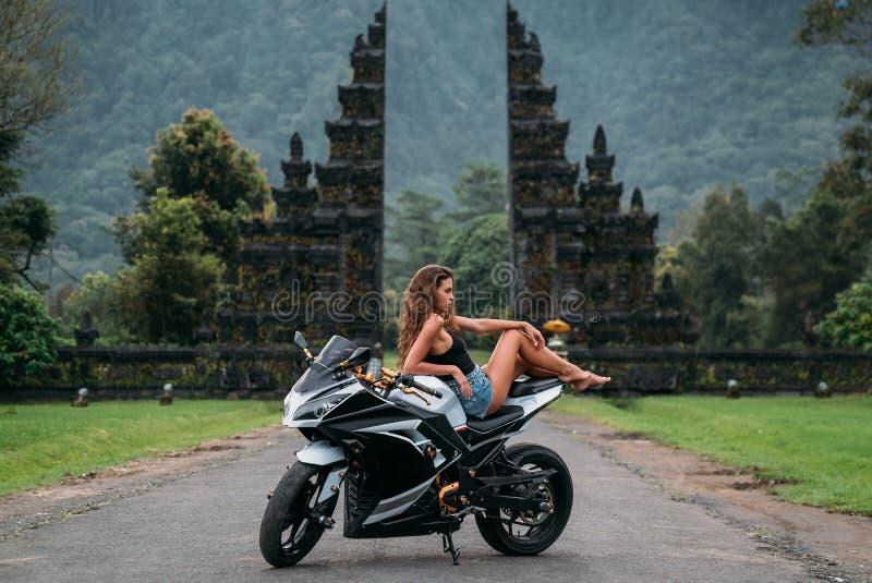 Het mooie sexy meisje zit op een motorfiets in zwart-wit Een model gekleed in het zwarte de borrels van Jersey en van het denim s stock foto