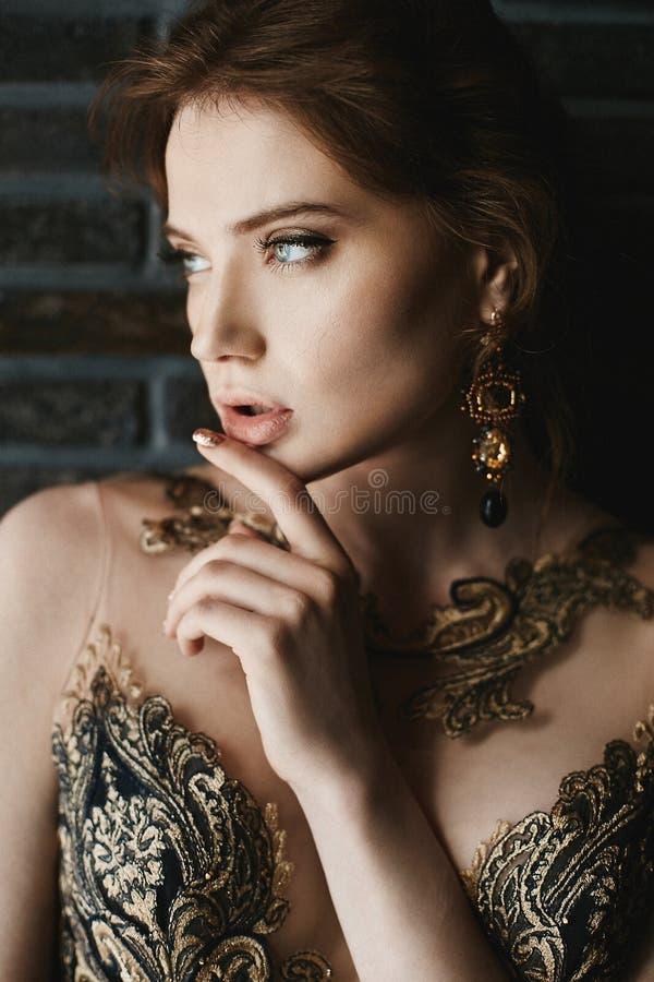 Het mooie, sexy, modieuze donkerbruine meisje met blauwe ogen, in gouden kleding met met de hand gemaakte gouden oorringen, stelt royalty-vrije stock fotografie