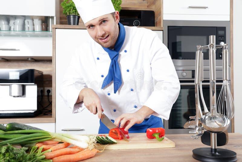Het mooie sexy vrouwenman paar als kok kookt in een keuken stock foto's