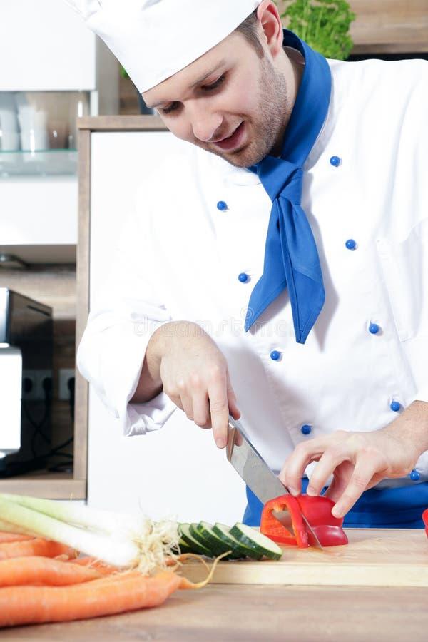 Het mooie sexy vrouwenman paar als kok kookt in een keuken stock fotografie