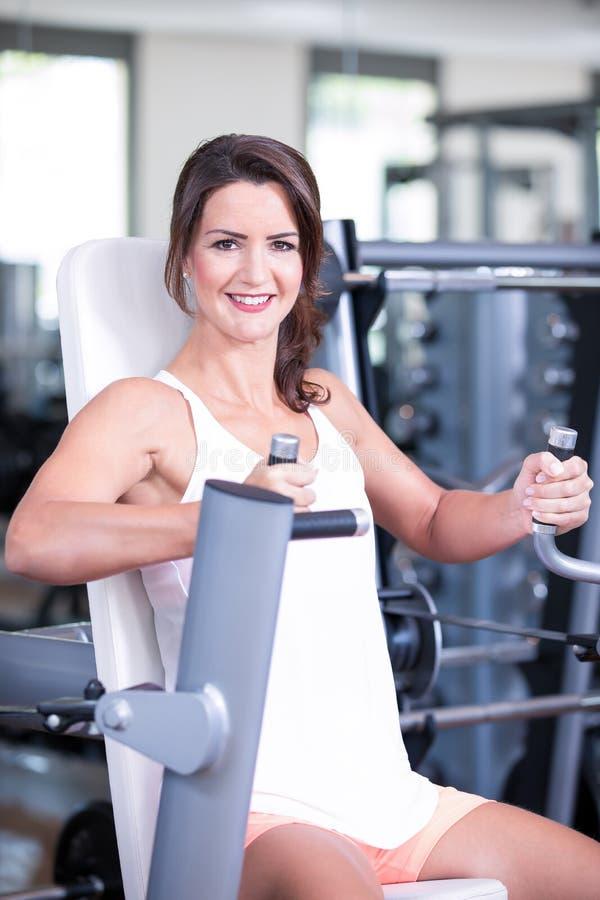 Het mooie sexy vrouwenman paar doet een training in de fitnesgymnastiek - borstpers, bank stock foto's