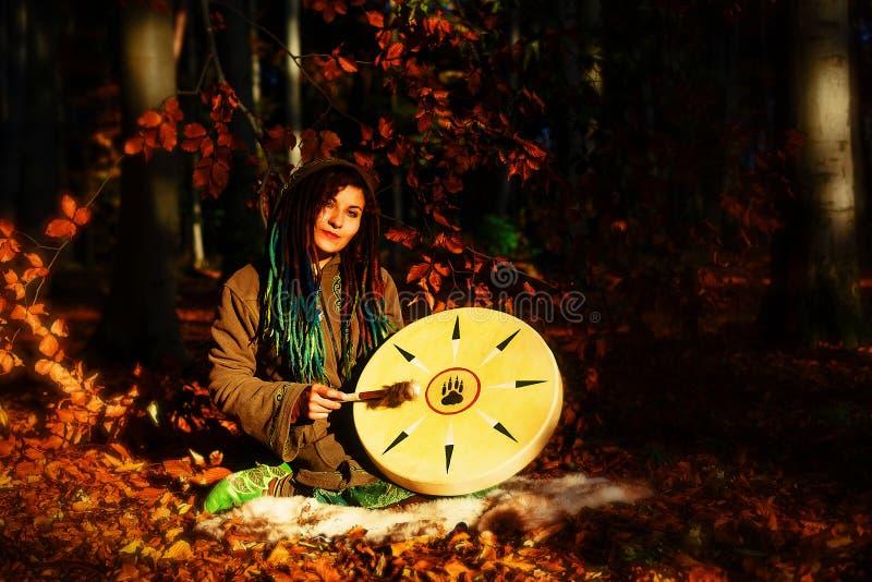 Het mooie shamanic meisje spelen op de trommel van het medicijnmankader op achtergrond met bladeren en bloemen stock fotografie
