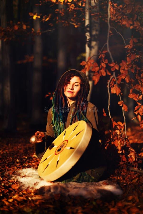 Het mooie shamanic meisje spelen op de trommel van het medicijnmankader op achtergrond met bladeren en bloemen royalty-vrije stock fotografie