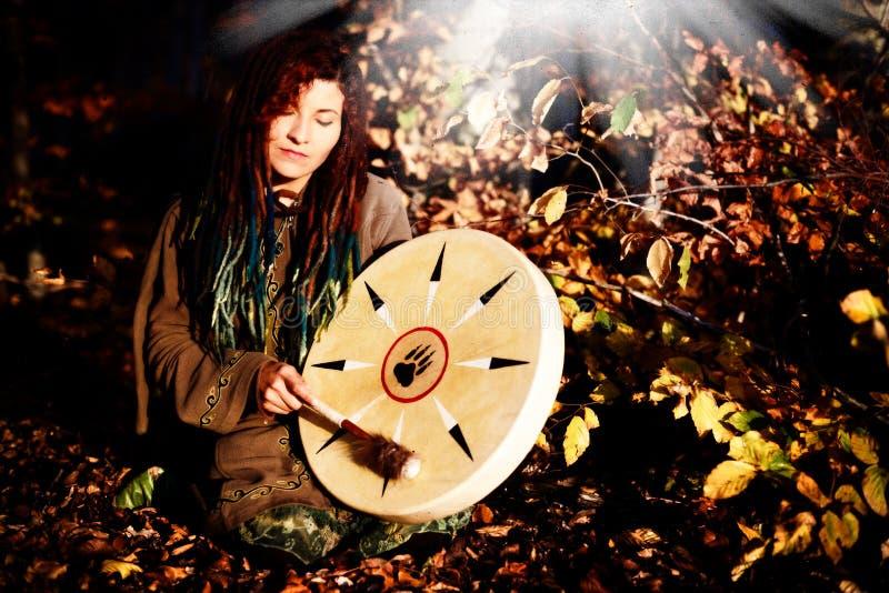 Het mooie shamanic meisje spelen op de trommel van het medicijnmankader op achtergrond met bladeren en bloemen royalty-vrije stock afbeelding