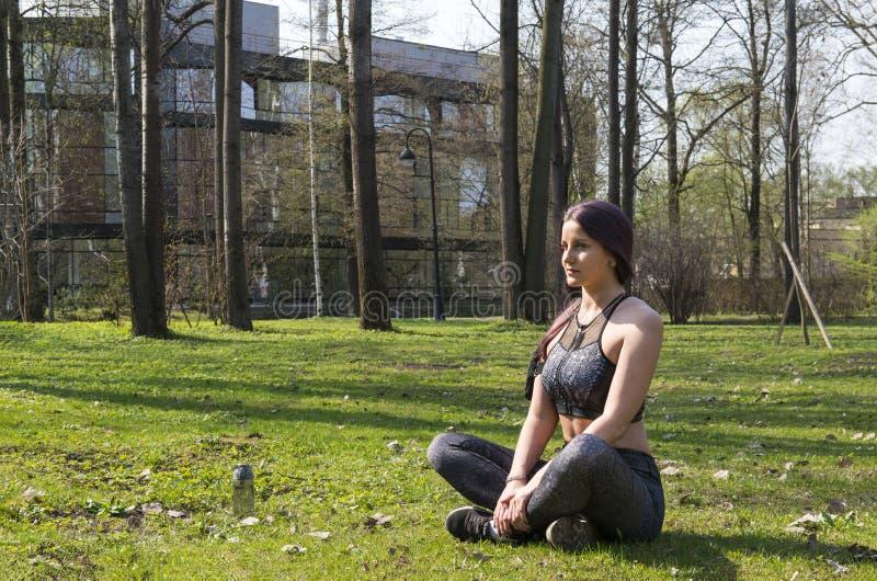 Het mooie slanke atletische meisje in sporten kleedt het zitten in een opheldering onder het groen in het Park in de Lotus-positi royalty-vrije stock fotografie