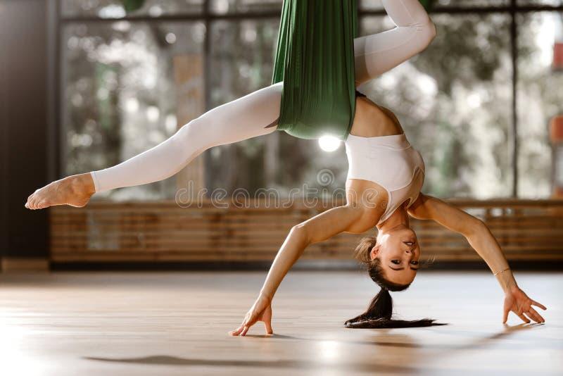 Het mooie slanke donker-haired meisje gekleed in witte sportenbovenkant en legging doet uitrekkende oefening op groene hangmat royalty-vrije stock foto's