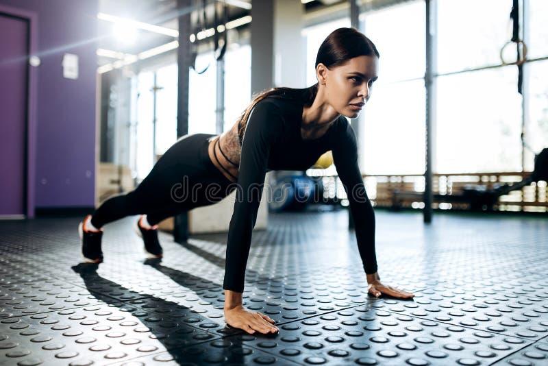 Het mooie slanke donker-haired meisje kleedde zwarte sportenkleren doet plank in de gymnastiek royalty-vrije stock foto's