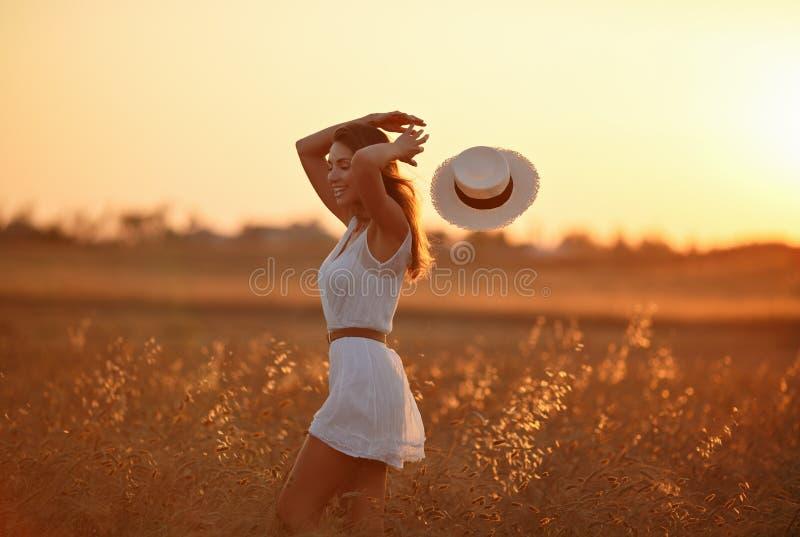 Het mooie slanke meisje in witte kleding en hoed loopt in stock foto's