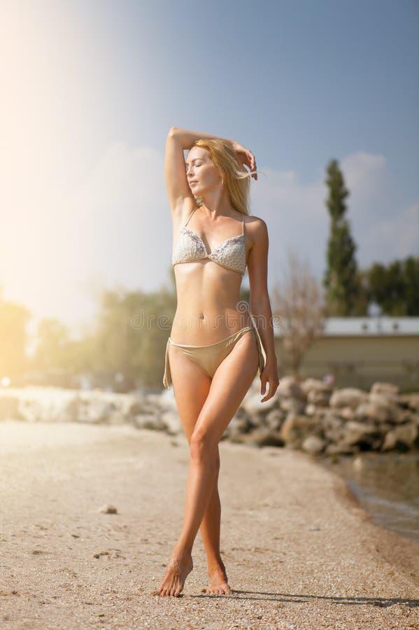 Het mooie slanke meisjesblonde in een beige modieuze bikini zonnebaadt op het strand in toevlucht stock foto's