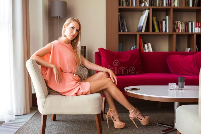 Het mooie slanke meisjesblonde in een modieuze roze de zomerkleding in hoge hielen zit op een stoel in een mooie woonkamer royalty-vrije stock fotografie