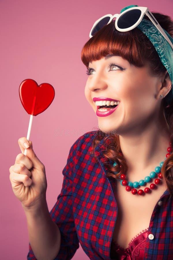 Het mooie speld-omhooggaande meisje stellen met rode hart-vormige lollyagai royalty-vrije stock foto