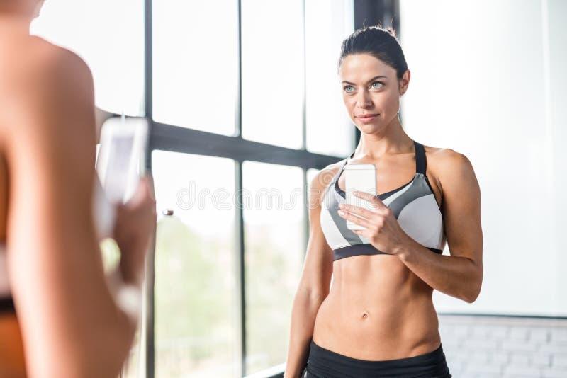 Het mooie Sportieve Vrouw het Glimlachen Stellen voor Spiegel Selfie in Gymnastiek stock afbeelding