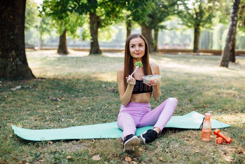 Het mooie sportmeisje eet salade in het Park stock afbeelding
