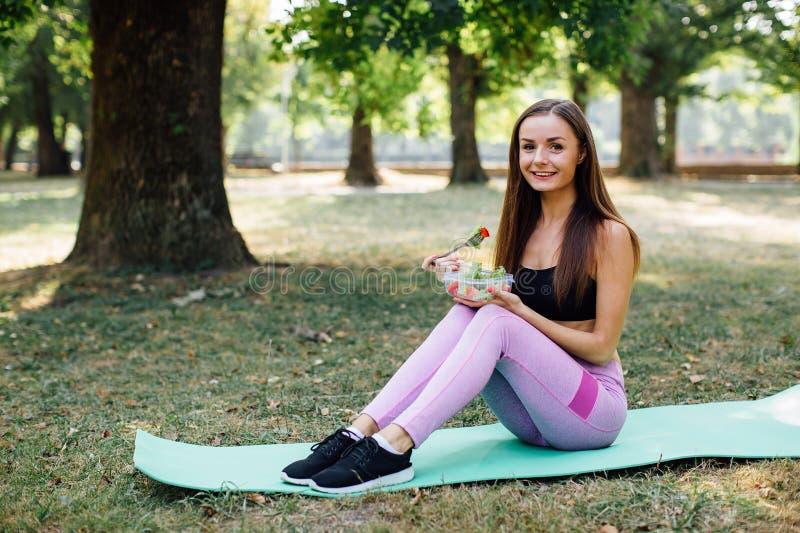 Het mooie sportmeisje eet salade in het Park royalty-vrije stock afbeelding