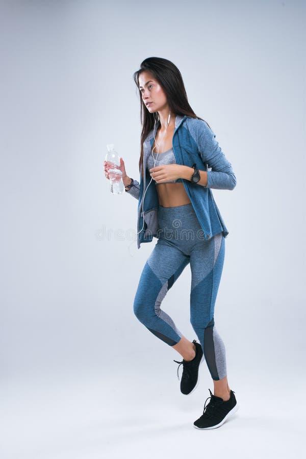 Het mooie sportmeisje loopt met fles water in oortelefoons en luistert aan muziek Volledige lengte die van sportenvrouw in studio stock foto's