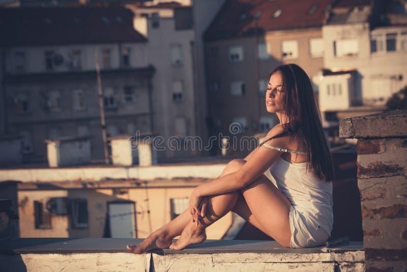 Het mooie stadsmeisje geniet van in zonsondergang bij dak volledige lichaam geschotene samenvatting royalty-vrije stock foto