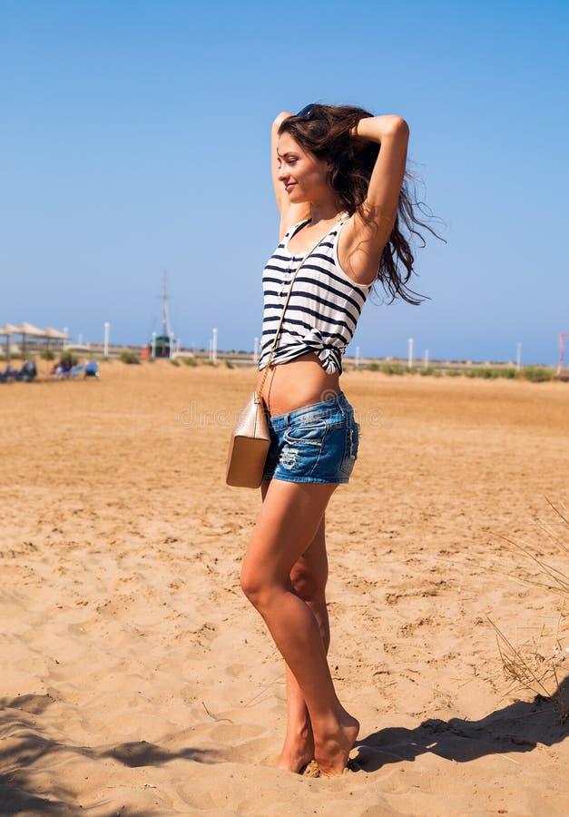 Het mooie sterke het genieten van vrouw stellen op het strand in blauwe shor royalty-vrije stock foto's