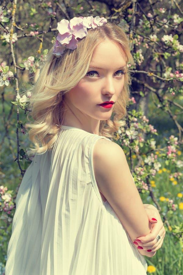 Het mooie tedere zoete jonge meisje met een kroon van bloemen in haar haar in een witte lichte kleding loopt in de weelderige tui stock foto