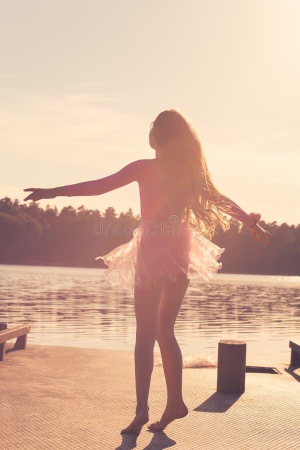 Het mooie Teen-meisje met lang stromend haar danst in de wind tegen de achtergrond van de zee stock foto