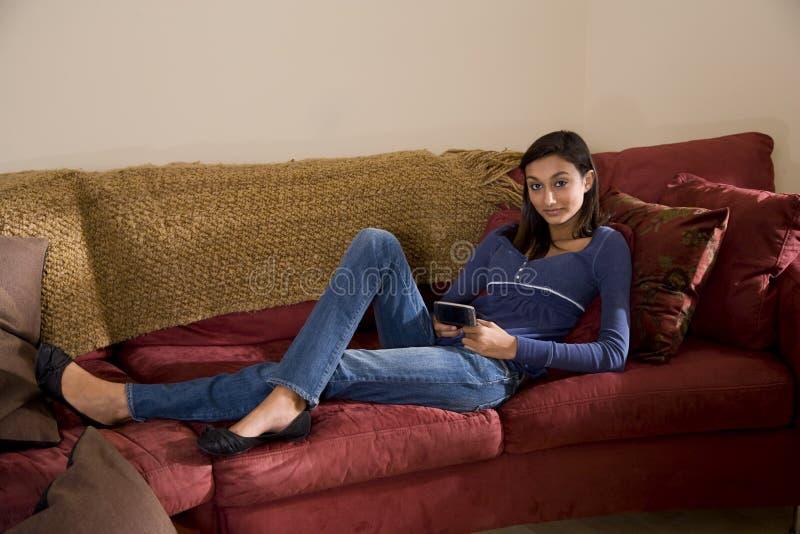 Het mooie tiener ontspannen bij bank het texting stock foto's