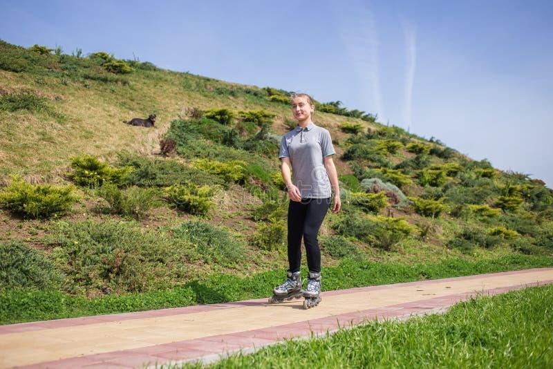 Het mooie tiener rollerskating in park royalty-vrije stock fotografie