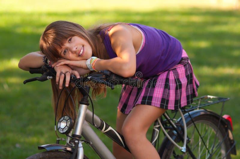 Het mooie tiener stellen op haar fiets royalty-vrije stock foto