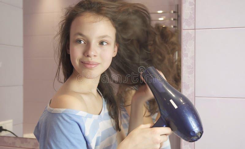 Het mooie tienermeisje droogt haar een hairdryer in badkamers royalty-vrije stock foto